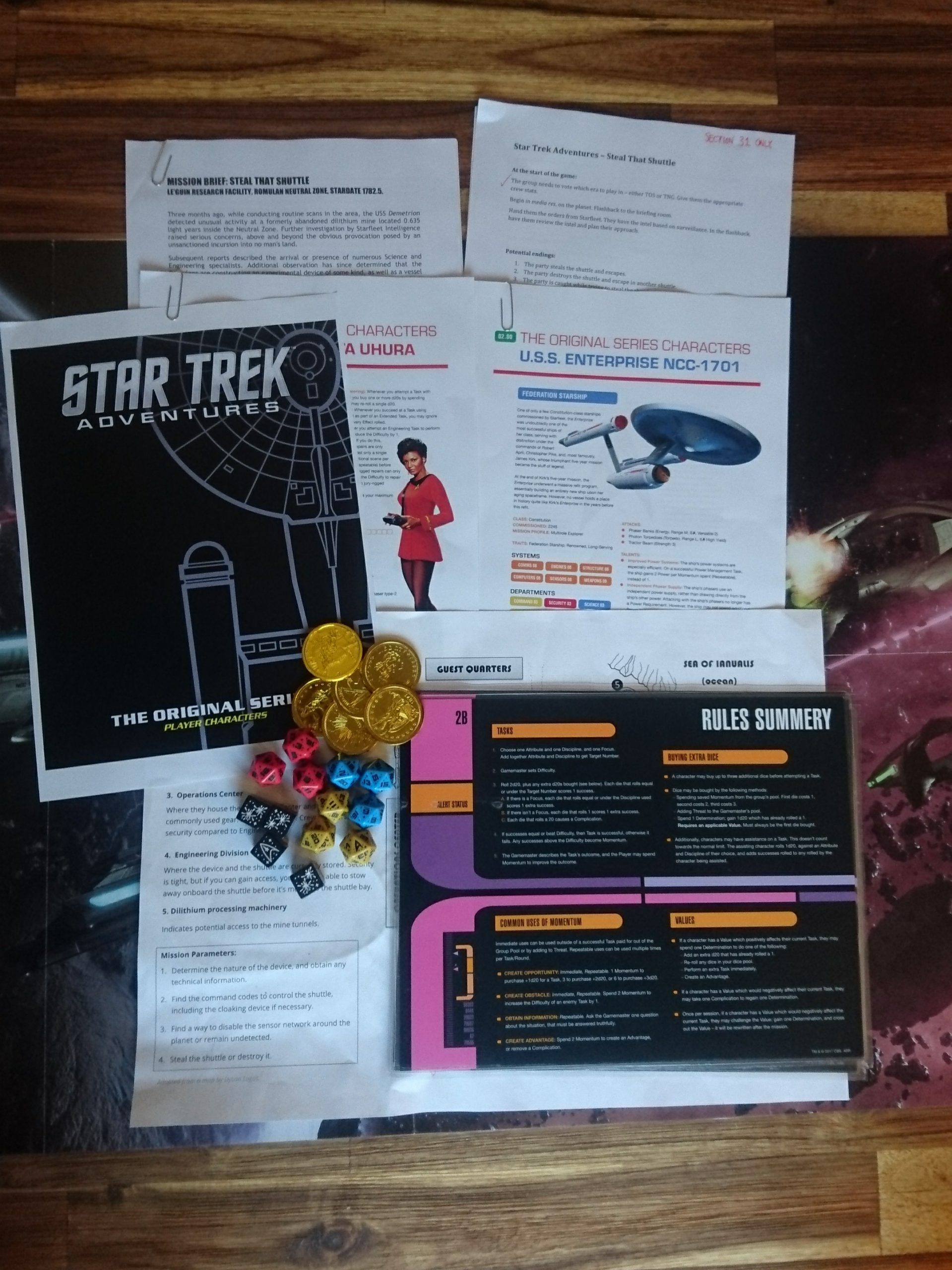 Miscellaneous items for a Star Trek Adventures game: Coins used as tokens, official dice, rules summaries, character sheets for Uhura and the Enterprise, the map, and the mission briefing for the GM.